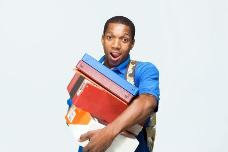 Male student wearing a backpack carries notebooks and boxes. He looks surprised. Horizontally framed photograph. photo