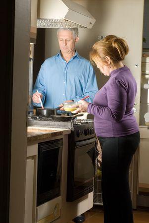 Een paar staande in hun keuken, het voorbereiden van een maaltijd, in de kachel. - Verticaal framed