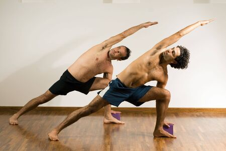 Two men performing a stretch, on hardwood floor. - horizontally framed