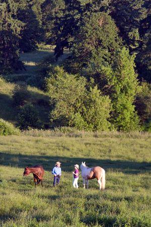 Twee mensen die hun paarden, staat in een weide van gras, met bomen. - Verticaal framed