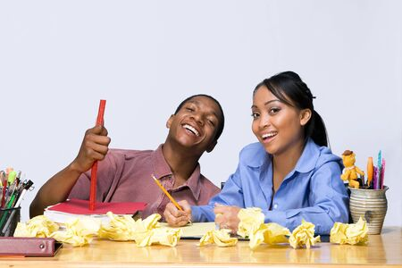 Two students laughing as they sit at a desk. Horizontally framed shot. Stock Photo - 3264032