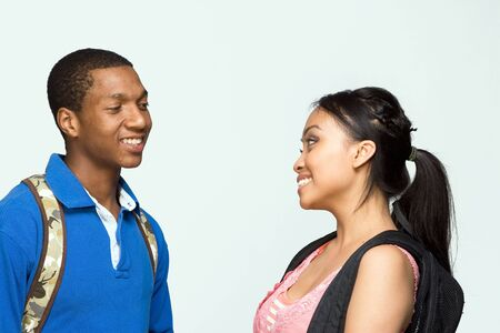 Two students wearing backpacks look at each other and laugh. Horizontally framed photograph photo