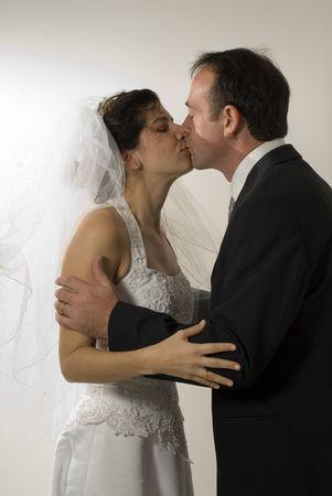 Een paar pasgetrouwden kus, terwijl men nog in hun huwelijk outfits. - Verticaal framed