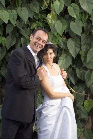 Newly weds glimlach op de camera, terwijl in hun huwelijk kleren. - Verticaal framed