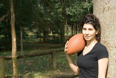 A young, attractive woman is standing next to a tree at the park.  She is smiling and holding a football on her shoulder.Horizontally framed photo. photo