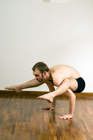 over shoulders: Man performing yoga. Arms supporting body, legs and feet draped over shoulders. Vertically framed shot.