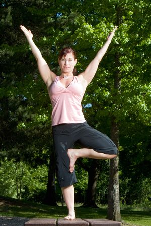 vertically: Physically fit woman standing on picnic table in the park. Posed in yoga position, balanced on right foot and smirking. Vertically framed shot.