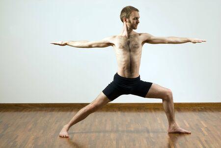 legs spread: Hombre la realizaci�n de ejercicio de yoga. De pie, piernas propagaci�n, los brazos estirados. Horizontalmente enmarcada disparo.  Foto de archivo