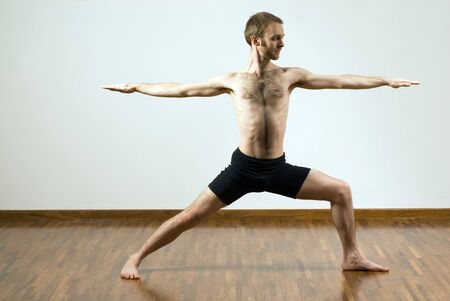spread legs: Man performing yoga exercise. Standing, legs spread, arms stretched. Horizontally framed shot.