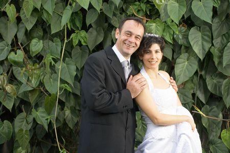Newly weds glimlach op de camera terwijl hij in het bezit elkaar, in hun bruiloft kleding. - Verticaal framed