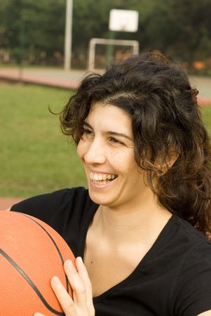 Young, attractive, happy woman is standing on an outdoor basketball court.  She is holding a basketball and smiling and laughing.  Vertically framed shot. photo