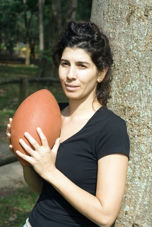Young, attractive woman is leaning against a tree.  She is holding a football.   Vertically framed shot photo