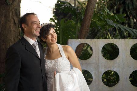 Een pas getrouwd paar glimlach, terwijl men nog in hun huwelijk kleren. Een natuurgebied vult de achtergrond. - Horizontaal omlijst