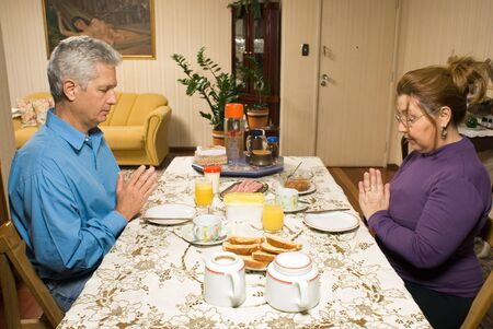 A couple pray at their dinner table before beginning to eat. - horizontally framed photo