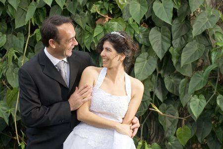Een pas getrouwd paar staren op elkaar, terwijl in hun huwelijk kleren. - Horizontaal omlijst