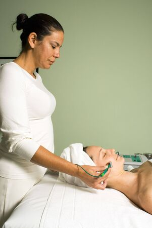 workplace wellness: Side view of a woman lying down receiving a facial. Vertically framed photograph.