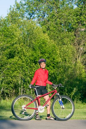 Woman standing next to bicycle smiling. Wearing sports gear and helmet. Natural background. Vertically framed shot. photo