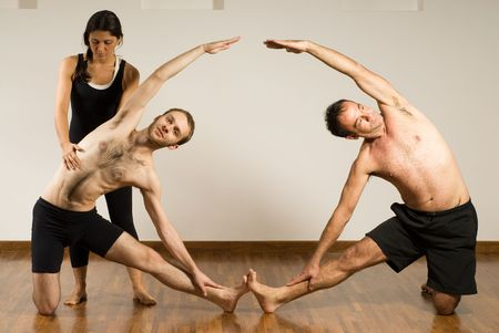 Two men in a yoga class, their feet are touching and their arms are arched towards each other in the air photo