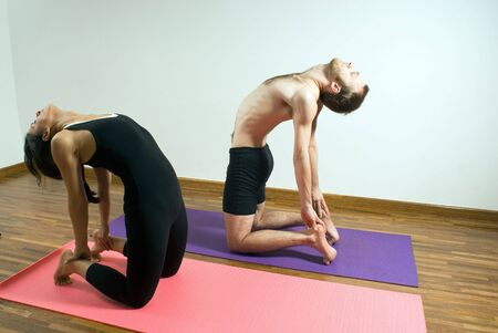 arching: Man and Woman arching their backs and holding their feet as they stretch. Horizontally framed photograph.