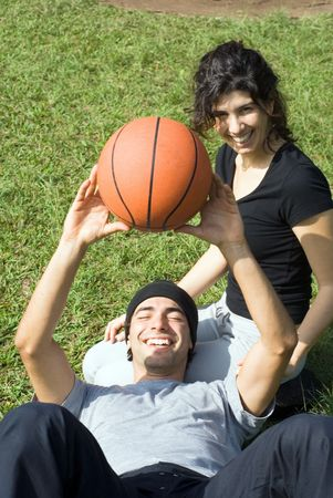 vertically: A couple is sitting on the grass in a park.  The woman is looking at the camera and the man is resting on the womans lap.  The man is holding a basketball above his chest.  Vertically framed photo. Stock Photo
