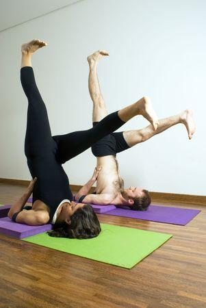 legs spread: El hombre y la mujer la realizaci�n de yoga junto a esteras. Ubicada en los hombros, los pies en el aire por encima de la cabeza, las piernas propagaci�n. Vertical enmarcada disparo.