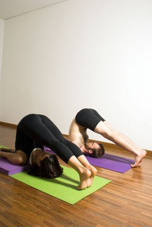 vertically: Man and woman performing yoga exercise. Lying on shoulders, feet and legs over head, eyes closed. Vertically framed shot.