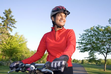 Close-up of woman standing next to bicycle and smiling. Wearing sports gear and helmet. Horizontally framed shot. photo
