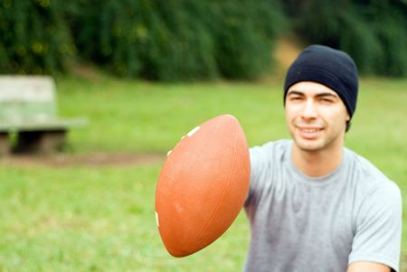 A man is sitting in a park.  He is smiling, looking at the camera and holding out a football.  Horizontally framed photo. photo