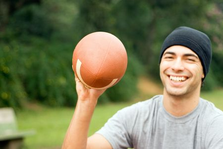 A man, sitting on the park ground, holds a football with one hand, smiling - horizontally framed photo