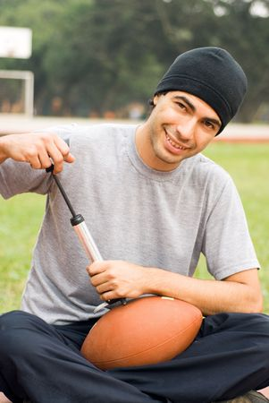 A man is sitting in a park.  He is smiling, looking at the camera and pumping air into a football.  Verticallly framed photo. photo