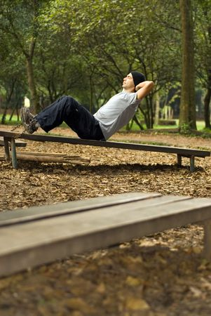 A male, exercising his ab muscles out, doing crunches, on a park bench - vertically framed