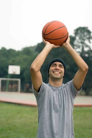 midlife: A man, in a park, stands tall, ready to shoot a basketball while smiling - vertically framed