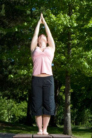 arms above head: Woman standing on picnic table in the park. Posed in yoga position, head back, arms above head in prayer formation. Vertically framed shot.