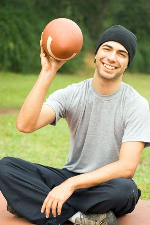 A man, sitting, holding a football, smiling for the camera - vertically framed photo