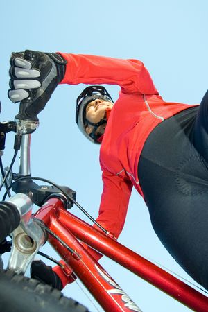 Close-up of woman standing next to bicycle smling. Wearing sports gear and helmet. Vertically framed shot. photo
