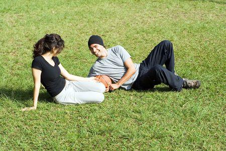 カップルは、公園の芝生の上に座っています。お互いを見て、男と女は。彼らはバスケット ボールを保持していると、お互いに笑みを浮かべてします。水平方向にフレームの写真。