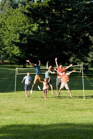 Group of kids jump happily as the stand in a park in front of a volleyball net - Vertically framed photograph. photo