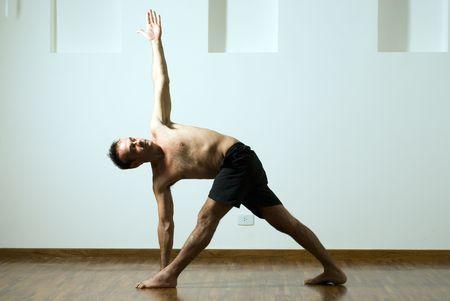 legs apart: Hombre en un yoga plantean con un brazo extendido y la otra hacia abajo y sus piernas. Horizontal fotograf�a enmarcada