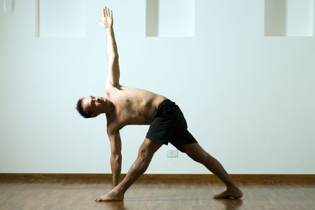 legs apart: Man in a yoga pose with one arm extended up and the other down and his legs apart. Horizontally framed photograph Stock Photo