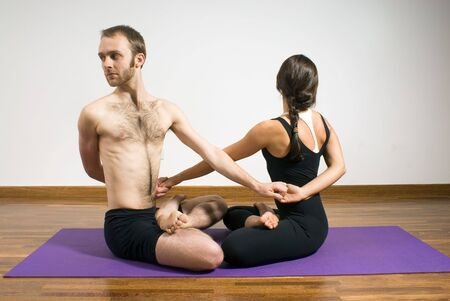 Man and woman practicing yoga with their arms entwined on a purple yoga mat. Horizontally framed photograph Stock Photo