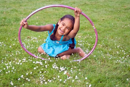 Little girl smiling in the grass playing with a hula hoop. Horizontally framed photograph Stock Photo - 3271310