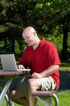 Man smiles as he works on his laptop on a park bench. Vertically framed photograph Stock Photo