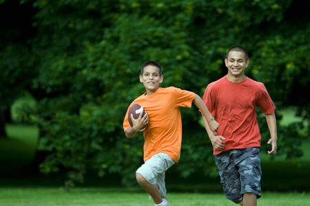 horizontally: Two boys playing football in a field.  Horizontally framed photograph.