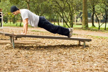 Een man op een bankje, doing push-ups, buitenshuis - horizontaal omlijst