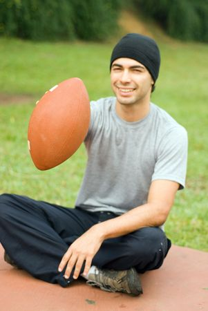 A man is sitting in a park.  He is smiling, looking at the camera and holding out a football.  Verticallly framed photo. photo