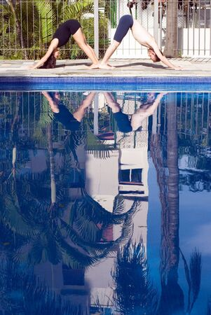 A couple, in a v-shape, stretch by the poolside - vertically framed