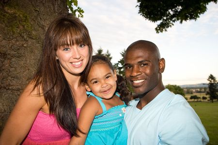 caucasian race: Happy family smiling as they pose by a tree. Horizontally framed photograph
