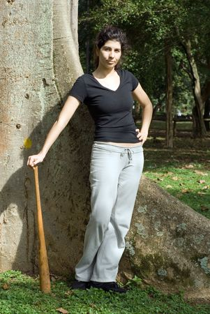 sternly: A woman is standing next to a tree at a park.  She is looking sternly at the camera.  She is posing with a baseball bat.  Vertically framed photo.
