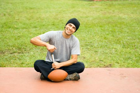 A man is sitting in a park.  He is smiling, looking at the camera and pumping air into a football.  Horizontally framed photo. photo