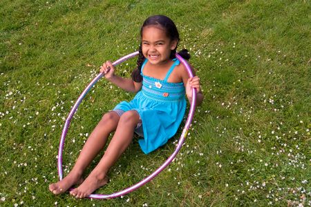 Little girl smiling in the grass playing with a hula hoop. Horizontally framed photograph Stock Photo